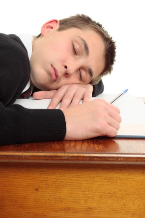 weary: A tired, weary or bored student at desk sleeping or resting. Stock Photo