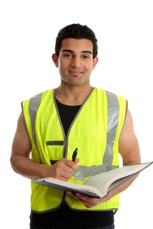 obrero: Un trabajador de la construcci�n masculina o otro jornalero sosteniendo una libreta y l�piz. Es buscar y sonriente. Fondo blanco.  Foto de archivo