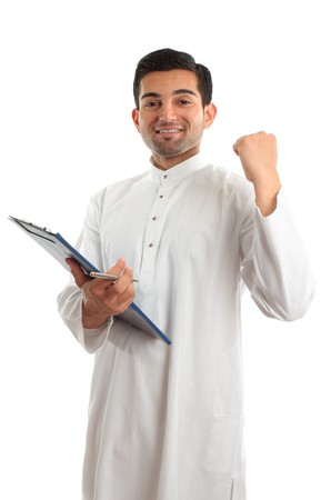 happy ethnic businessman wearing traditional robe, durta, dishdasha, holding a file folder and with hand clenched in a victorious fist. photo