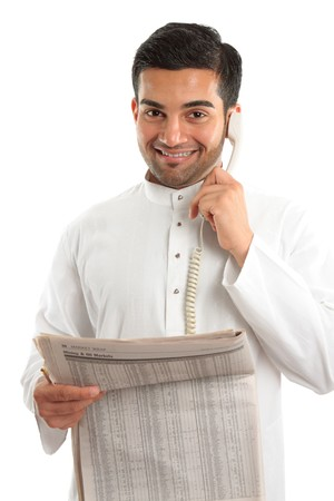 qameez: An ethnic italian  arab mixed race businessmanwearing traditional middle eastern clothing.  He is on the telephone and holding a newspaper at finance section.  White background.