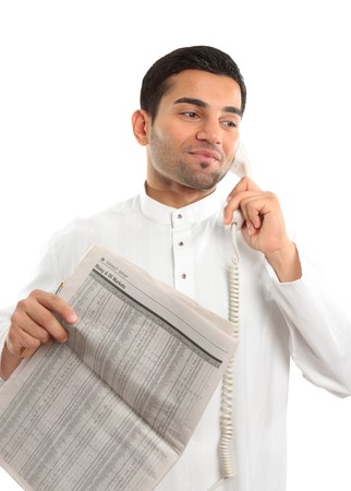 thoub: An ethnic mixed race man on a telephone call.  He is holding a newspaper and wearing traditional middle eastern clothing.  White background.