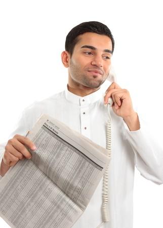 middle eastern clothing: Un uomo di razza mista etnica su una chiamata telefonica. Egli � azienda un giornale e indossando abiti tradizionali mediorientale. Sfondo bianco.