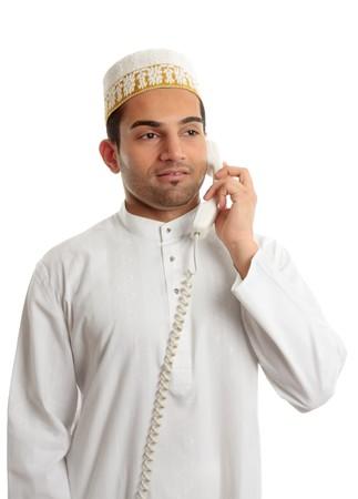 qameez: An arab italian mixed race businessman on the telephone.  Stock Photo