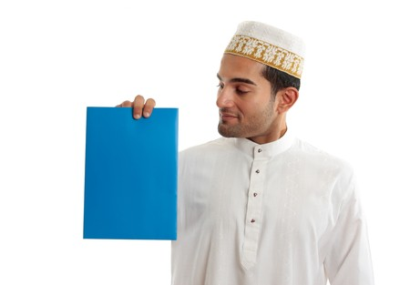 kameez: An ethnic mixed race man wearing traditional arab clothing, is holding a brochure, sign, document in hone hand and looking at it.  White background. Stock Photo