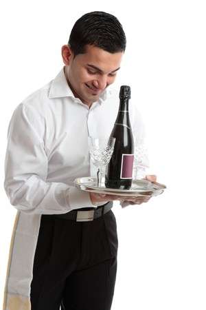 A smiling waiter, bartender, servant or attendant carrying a wine bottle and glasses.  White background. photo