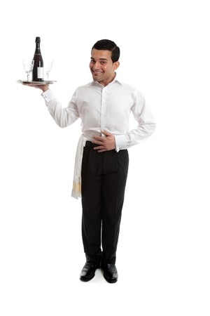 Smiling waiter, butler, bartender ot other attendant holding a silver tray with a bottle or wine and glasses.  White background.