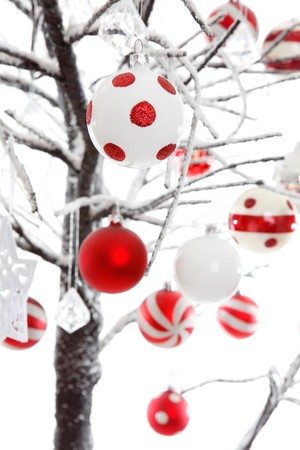 Christmas baubles and ornaments hang from snow covered branches.