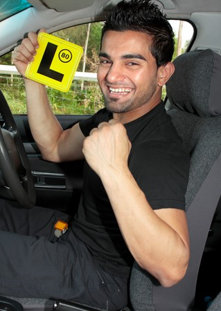Happy male driver holding L learner plates and sitting in a car. photo