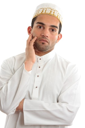 kameez: A man wearing cultural ethnic robe and decorative topi thinking.  White background.