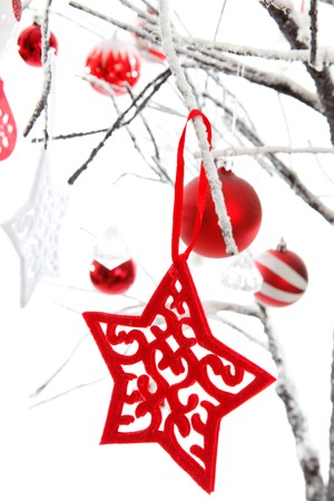 Christmas stars, baubles and other decorations hang from snow covered branches. White background