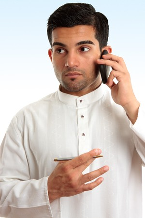 qameez: Ethnic mixed race businessman wearing traditional robe is using a mobile phone and looking sideways.