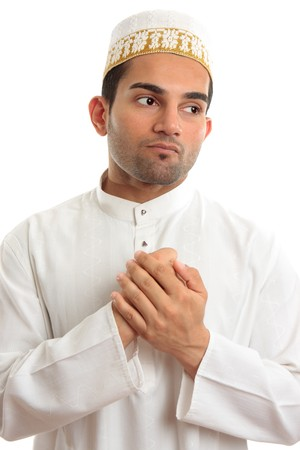 thoub: An ethnic man in traditional robe holding two hands to his chest and pondering.  White background.