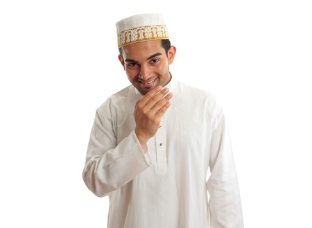 qameez: Smiling friendly ethnic man wearing a traditional embroidered robe with ruby buttons and a white and gold embroidered topi hat.  White background. Stock Photo