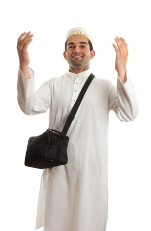 kameez: Ethnic mixed race man wearing white embroidered robe  and topi hat and carrying black shoulder bag and arms raised in praise or joy