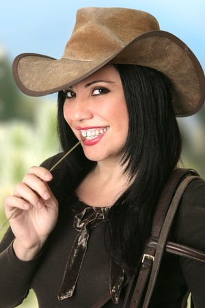 akubra: A smiling cowgirl country girl smiling and chewing on a piece of lucerne hay against a mountain landscape.