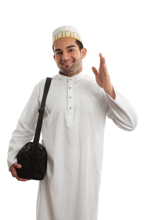 A man wearing a beautiful embroidered robe, thobe, kurta outfit fastened with ruby buttons and wearing a decorative topi hat.  photo