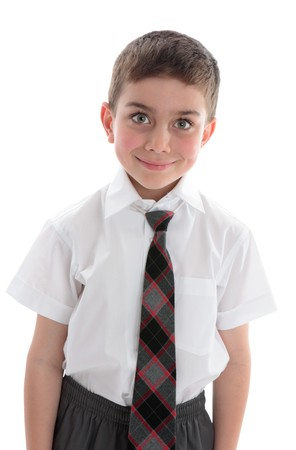 A beautiful young boy school child wearing school uniform.  White background. photo