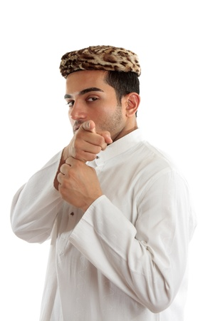 kameez: Ethnic man pointing his finger at you or something else.  He is dressed in cultural clothing.  White background.