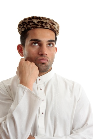 thoub: An ethnic man wering a white embroidered robe fastened with claw set rubies and wearing vintage leopard skin hat.  He is looking up and thinking or pondering.   Space for copy.   White background.