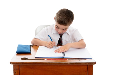 scholastic: A young boy wearing a school uniform sitting at desk writing in a book.  White background. Stock Photo