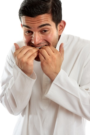 italian ethnicity: An ethnic man hunched over and  biting fingernails.  He may be scared or have anxiety, stress or other fears or worries.  White background.