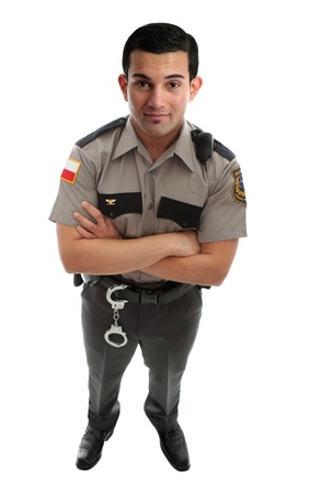 A male prison guard warden or policeman in uniform with duty belt and radio unit.   Standing with arms crossed and looking up.  White background Stock Photo - 8421275