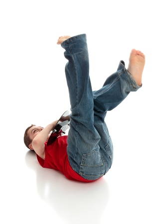 A little boy having fun playing a guitar.  He is lying on the ground with legs flailing in the air.  White background. photo