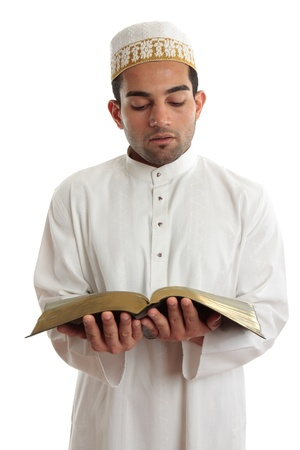 a righteous person: Man wearing cultural clothing is reading or studying a religious holy book.  White background. Stock Photo