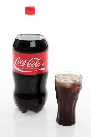 editorial: Bottle of Coca-Cola and Coca-Cola glass filled with coca-cola and ice.  Editorial Use Only.  White Background.