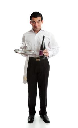 Smiling waiter, bartender or servant holding a bottle of  wine and glasses on a platter. photo