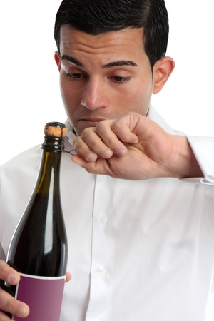 Closeup of a man or bartender holding and opening a bottle of wine or champagne.  White background. Stock Photo - 8804879