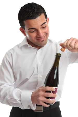A man or waiter removes a cork from a bottle ready for a celebration.  White background. photo