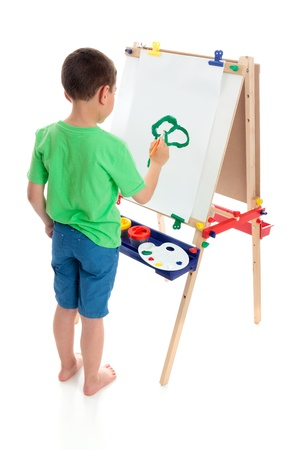 A young boy painting a picture on an art easel.  White background.