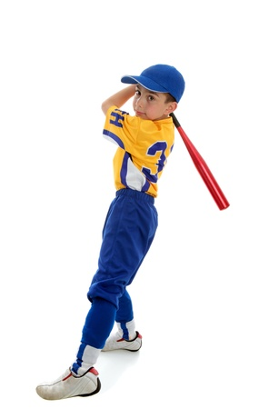 A young boy in a softball, baseball or t-ball uniform swings a bat.  White background. photo