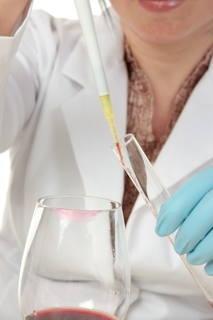 criminologist: A forensic investigator or criminologist uses a pipette to take a sample of the contents inside a glass for analysis.  Focus to pipette.