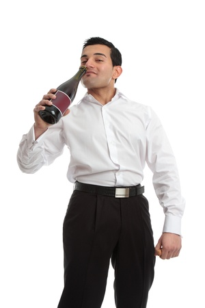 uncoordinated: An enebriated man staggers and drinks swigging wine directly from a bottle. Stock Photo