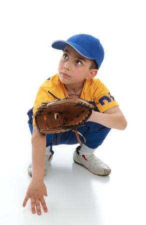 Ein wenig junge Baseballspieler hockend nach unten mit einem Mitt.  Platz für Kopie.
