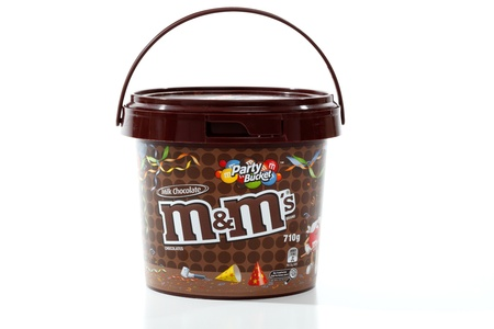 confectionary: M&Ms party bucket 710g of sweet colourful button shaped candy coated chocolate confectionary.  Made by Mars Inc, since 1941.  White background, editorial use only.