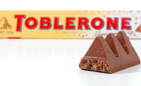 nougat: Toblerone chocolate containing honey and almond nougat and crispy rice pieces. Toblerone packaging in background  Toblerone is made in Switzerland by Kraft Foods.  Focus to foreground pieces.