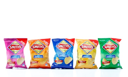 crisps: Five 45g packets of Smiths crinkle cut potato chips.  From left to right, Salt and Vinegar (924kj), Barbeque (941kj), Original (958kj), Cheese and Onion (945kj) and Chicken (939kj)   Smiths is owned by PepsiCo.  White Background.  Editorial Use Only.