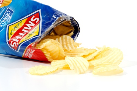An opened 45g packet of Smiths Potato crinkle cut chips with the crisps spilling out of the packet.  Smiths chips are owned by PepsiCo.  Photographed on a white background.  Editorial Use Only.