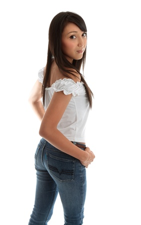 Beautiful young  woman wearing jeans and looking back over her shoulder.  Pretty mixed race asian caucasian girl.  White background.  Space for copy.  