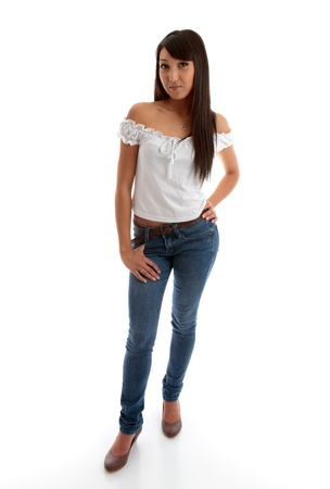 A lovely mixed race young woman wearing skinny jeans and a white gathered off the shoulder white top.  She is standing with one hand on hip, on  white studio background.
