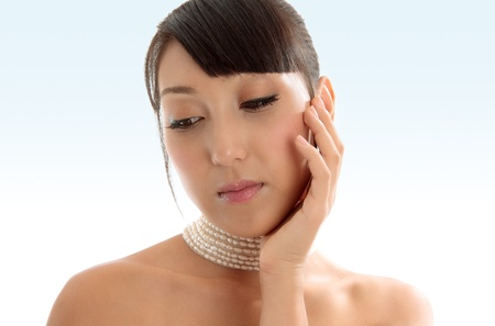 Attractive demure woman pondering quietly.  She has bare shoulders and one hand to her face and she is wearing a choker necklace accessory.  Model  Jessica Elms  (n.b. new model  would like some tearsheets of images in use,if you are able to forward a pro photo