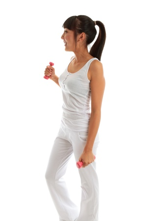 Beautiful young and happy girl exercising with hand weights to build muscle, firm and tone. She is wearing white pants and tank top.  There is motion in her hands and weights.  White background.