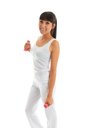 A beautiful attractive girl exercising using 0.5kg hand weights.  She is wearing white sportswear and smiling.  White background. Stock Photo - 9013497