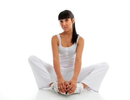 A young woman wearing fitness sportswear.  She is doing a groin and inner thigh stretch sitting on the floor with feet together and using effort to push knees to or close to the floor as possible.  White background with space for copy.  Model Jessica Elms Stock Photo - 9013488