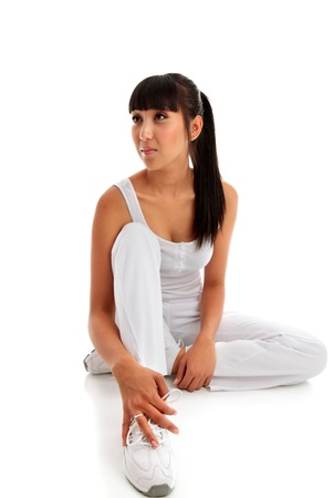A young beautiful woman wearing fitness clothing and sitting on a white background.  She is looking sideways.  Pretty mixed race girl asian caucasian.  Space for copy.  Model Jessica Elms, Makeup Hanae Satomura, Hair by Kayla Cifelli Stock Photo - 9013489