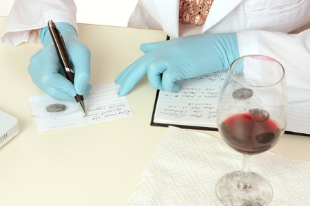 A crime scene forensic scientist obtains fingerprints from a glass using latent powder and tape and then writes down details.  Details are fictitious. Stock Photo - 9013503