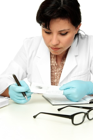 A female forensic scientist holds a fingerprint sample ready for further analysis. photo